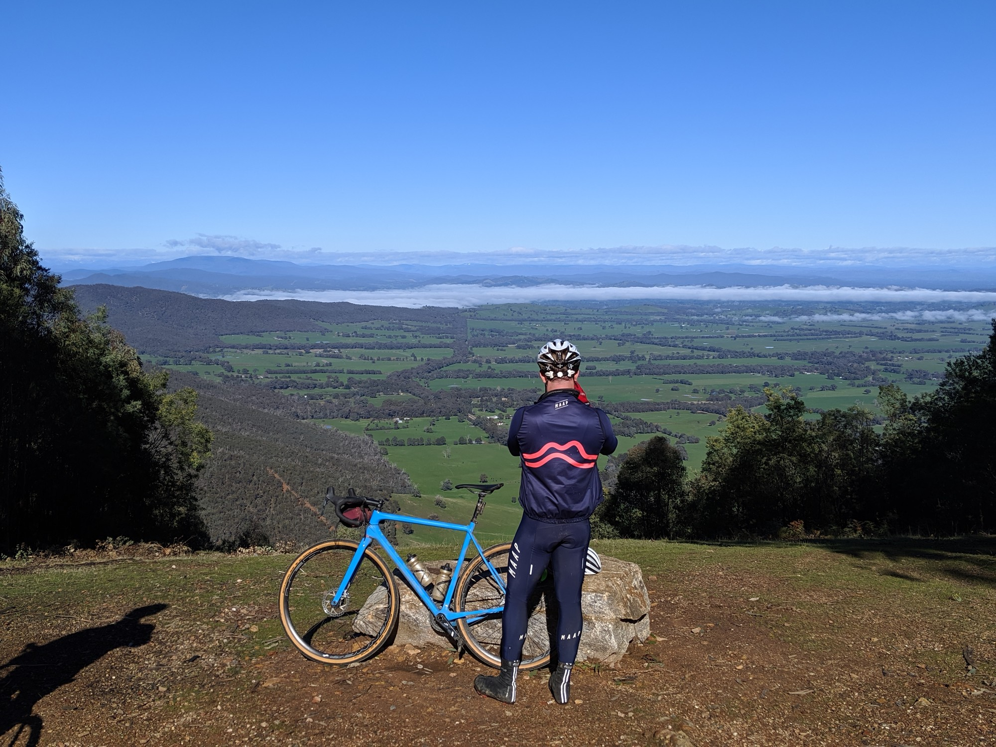 A gravel cyclists taking a photo at a lookout near Beechworth