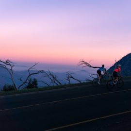 Two women cycling up a mountain with a backdrop of a pink and blue sky